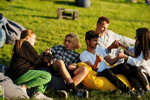 Fotografie, Obraz Young multi ethnic group of people watching movie at poof in open air cinema