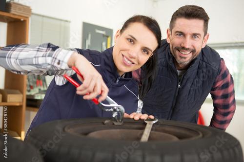 Fototapeta female mechanic repairing a car in a garage obraz