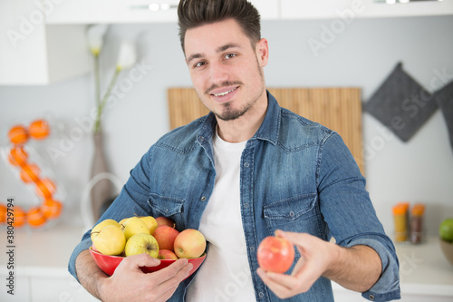 Fototapeta young handsome guy is holding a bowl of apples obraz