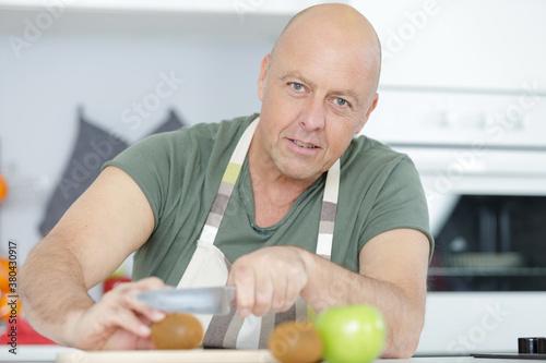 Fototapeta mature man preparing a green salad obraz