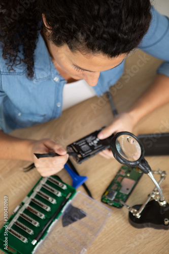 Fototapeta female repairing watch in her workshop obraz