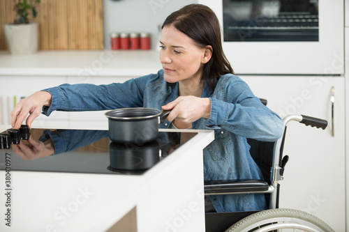 Fototapeta disabled woman in wheelchair boiling water in the kitchen obraz