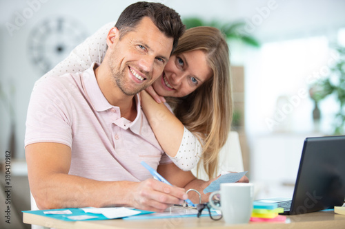 Fototapeta positive young couple calculating the bills at home obraz