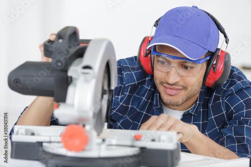 Fototapeta portrait of worker by industrial circular saw obraz