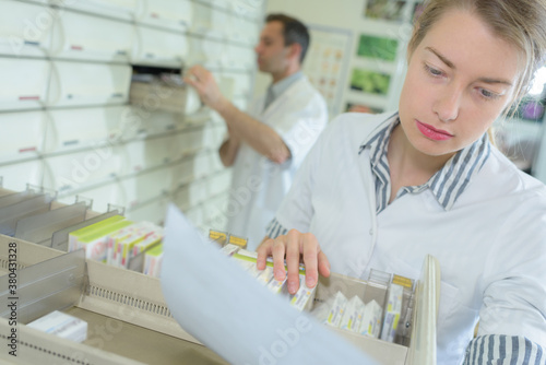 Fotografiet pharmacist inspecting the availability of the order
