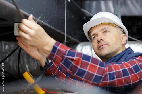Fototapeta electrician using a multimeter to test spotlight connections obraz