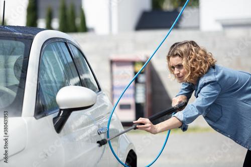 Fototapeta woman foaming her car with sponge obraz