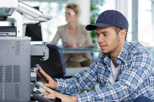 Fototapeta a technician fixing a printer obraz