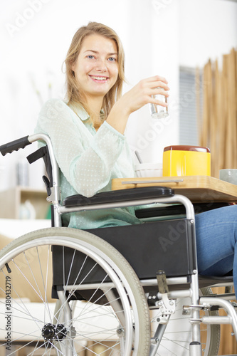 Fototapeta young woman in wheelchair having breakfast obraz