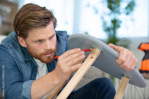 Fototapeta carpenter man marking a small woden table obraz