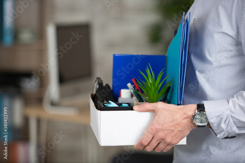 Fototapeta cropped view of person carrying box of workplace possessions obraz