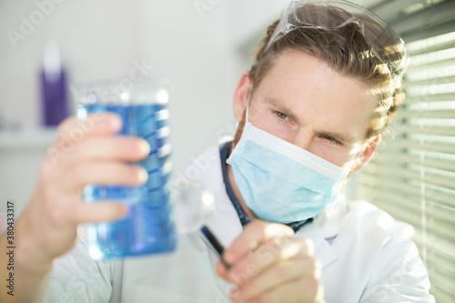 Fototapeta scientist wearing mask and holding beaker of blue liquid obraz