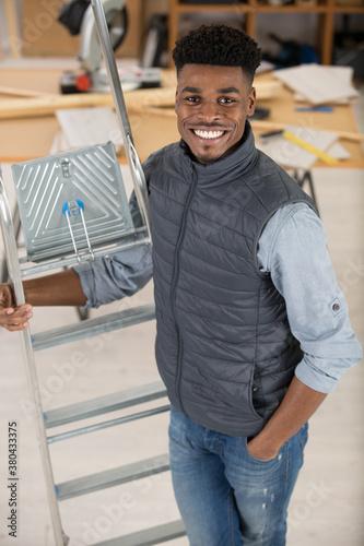 Fototapeta worker smiling holding ladder obraz
