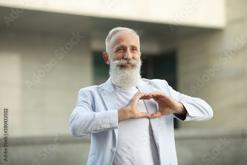 Valokuva Lovely good-looking caucasian bearded senior man and making heart gesture, expressing his feelings and tenderness while standing against street background