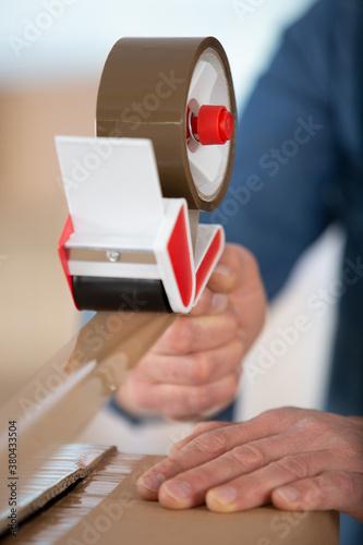 Fototapeta man using tape and cardboard box packing their belonging obraz