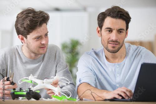 Fototapeta two male friends assembling drone obraz
