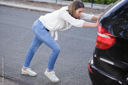 Fototapeta woman pushing a broken down car obraz