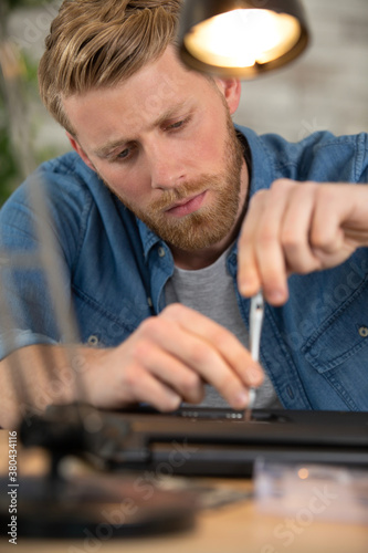 Fototapeta young male engineer repairs a laptop obraz