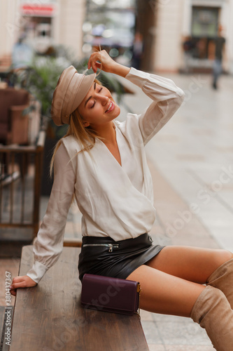 Fototapeta Blond smiling european woman in trendy autun  cap posing outdoor. Wearing white blouse and leather skrt and knitted block  thigh high boots in beige. obraz
