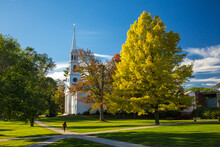 A Girl Walking On A Path By A Traditional American White Church With High Steeple.  Trees Are Showing Autumn Fall Colors.  Williamstown, MA
