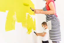 Woman And Kid Painting Their Home By Rollers