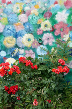 Red Roses In Front Of A Flower Mural