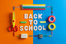 Schools Supplies On A Blue And Orange Cardboards With Back To School Message