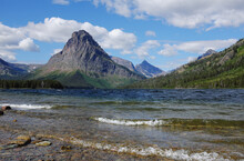 Waves Rolling Onto The Pebbled Shore Of Two Medicine Lake With Sinopah Mountain Dominating The Background.