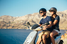 Happy Couple On A Moped Enjoying The View Over The Ocean In Kalymnos, Greece