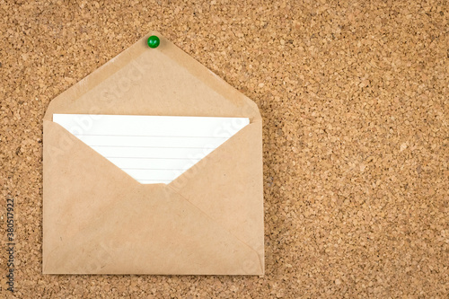 Valokuva Craft envelope is pinned to a cork board, in the envelope a white lined sheet of