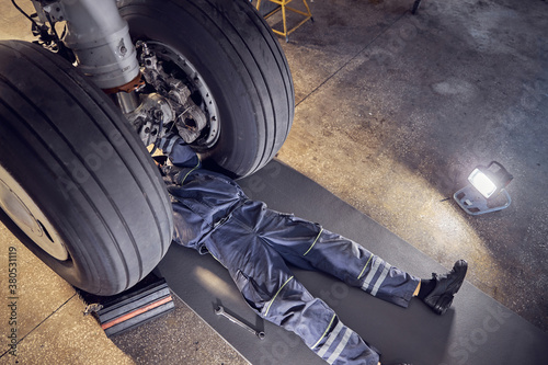 Wheels of the airplane with male mechanic in the aviation hangar Canvas Print