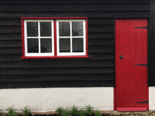 Outbuilding With Red Door And Window Frames.