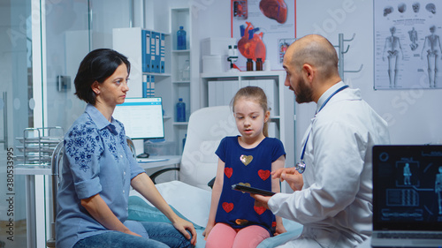 Fotografia Male doctor writing child diagnostic on tablet talking with woman