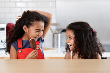 Happy Little Girls Laughing Together While Eating Ice Cream Bars