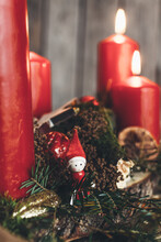 Little Helper From Santa Claus With A Red Jelly Bag Cap On An Festive Decorated Advent Wreath