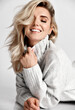 Portrait of young wealthy sexy smiling blonde woman model in cosy warm knitted sweater