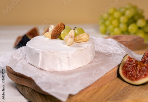 Slika na platnu Camembert cheese on wooden board, branch of green grapes , slice of figs and nuts