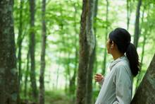 森の中で音楽を聴く女...