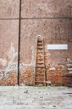 Ladder Against Brick Wall With Painted White Rectangle