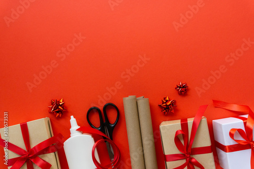 Christmas flat lay of gift boxes with wrapping craft paper, scissors, glue and decorations on red background, copyspace