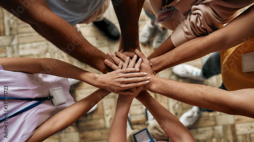 Fototapety, obrazy: Top view of diverse young volunteers putting their hands on top of each other like a real team while standing in charitable organization office