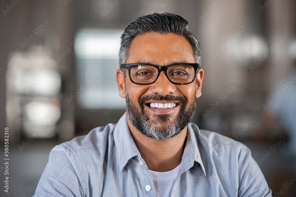 Fototapeta Smiling indian man looking at camera