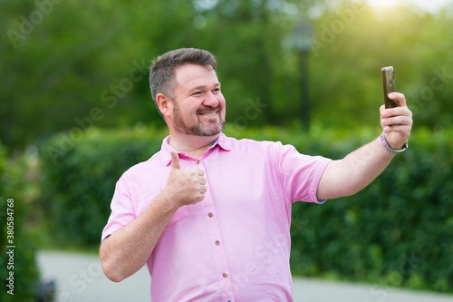 Cheerful fat man with a beard takes pictures of himself on a smartphone, selfie Canvas Print