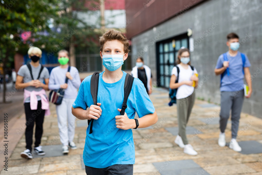 Fototapeta Portrait of teenager in protective mask with backpack going to school lessons on sunny autumn day. New lifestyle during coronavirus pandemic