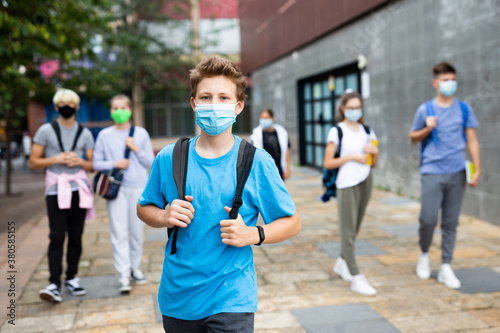 Photographie Portrait of teenager in protective mask with backpack going to school lessons on sunny autumn day