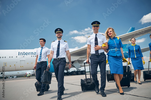 Cheerful pilots and stewardesses carrying travel bags at airport Canvas Print