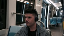 Young Guy Sitting Inside A Moving Train While Listening Music By Headphones At The Underground Metro In Montreal, Quebec, Canada.  -close Up Shot