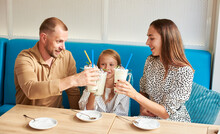 Happy Family - Mom, Dad And Daughter Are Sitting In The Local Cafe On A Blue Sofa Having Drinks, Clinking Glasses With Milkshakes. Plates And Cocktail Spoons On The Table