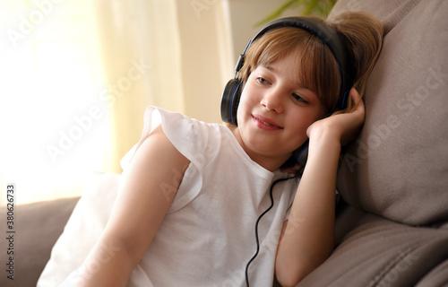 Obraz na plátně Girl listening to music carefully sitting on the sofa at home