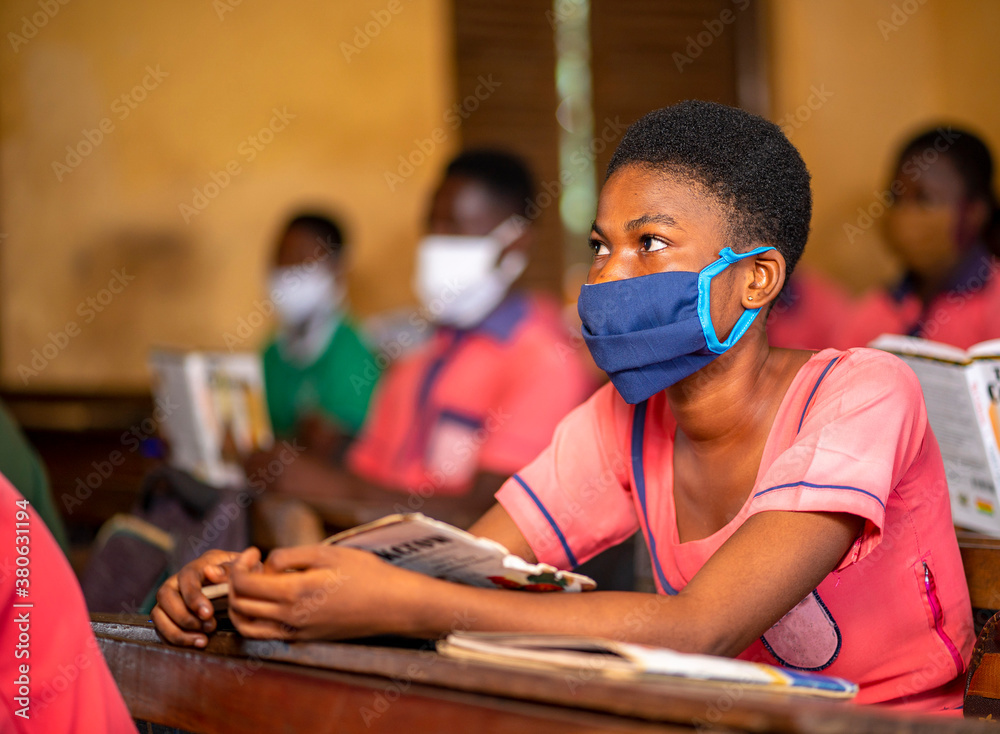 Fototapeta image of African lady with face mask with her colleagues blurred at background- classroom concept
